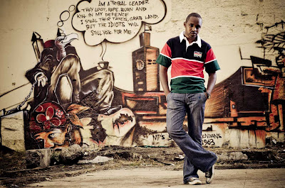 "Boniface Mwangi stands against his ""subversive"" grafitti painting he called ""Vultures""."